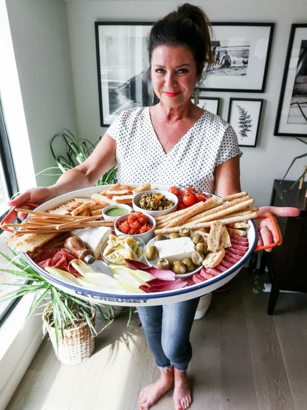 woman holding a Bruschetta Tray with crackers, cheese, and salami