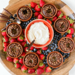 a round wood dessert board with lava cakes, fruit, and whipped cream