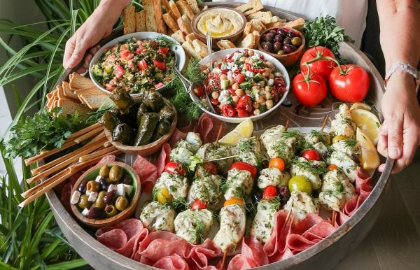 fish kebabs served on a round tray of food and salads