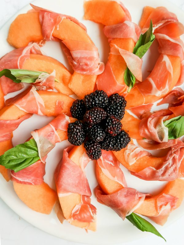 plate of Prosciutto-Wrapped Melon slices with berries in the center