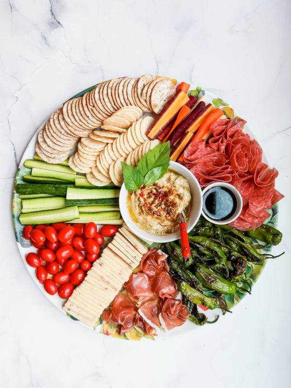 a round tray with cheese, meat, crackers, veggies, and hummus