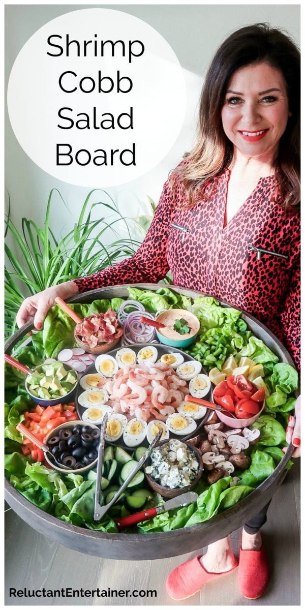 woman in red blouse holding a big red board filled with shrimp salad ingredients