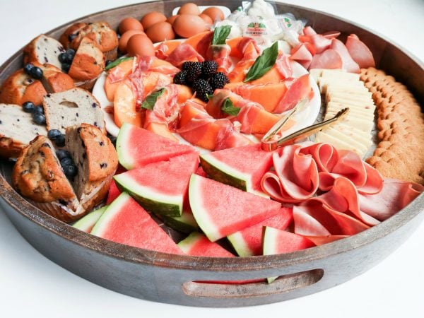 food tray with fresh watermelon, ham, cheese, muffins for brunch board