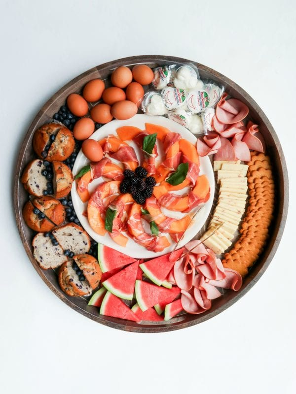 a Ham Cheese Brunch Board with a plate of melon slices in the center