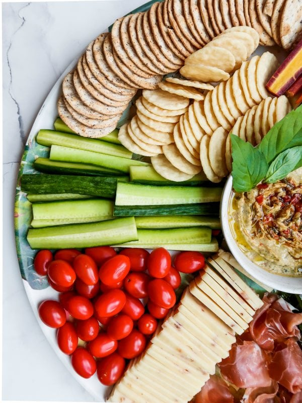 tomatoes, cucumber sticks, and crackers on a cheese board with hummus