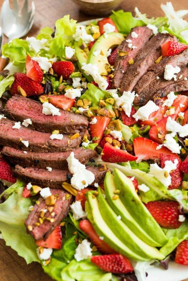beautiful sllices of steak and avocado on bed of greens with strawberries
