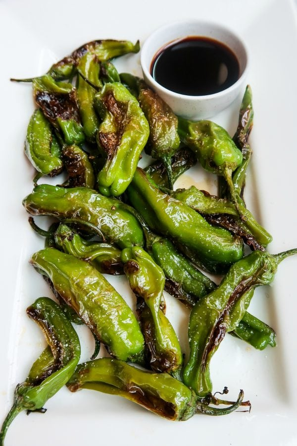 a plate of Shishito Peppers with dipping sauce