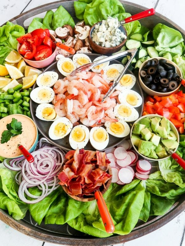 shrimp in the middle of a big salad, surrounded by hard cooked eggs, and salad toppings