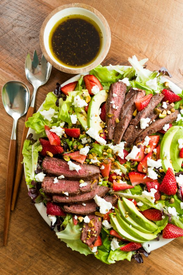 grilled steak salad with strawberries and avocados and small round bowl of dressing