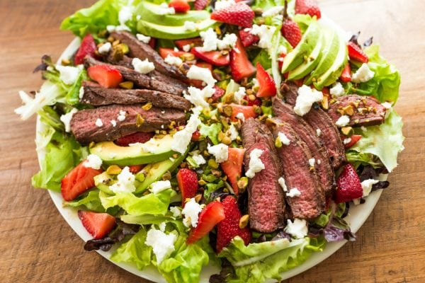round plate of green salad with steak, avocados, strawberries, and cheese