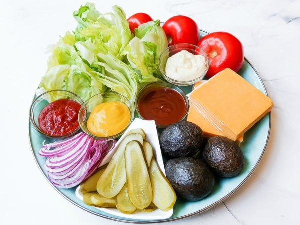 a close up of iceberg lettuce on a Basic Burger Condiment Platter, with tomatoes, avocados, cheese, red onion, etc.