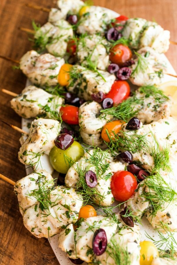 fish skewered with tomatoes, olives, and herbs