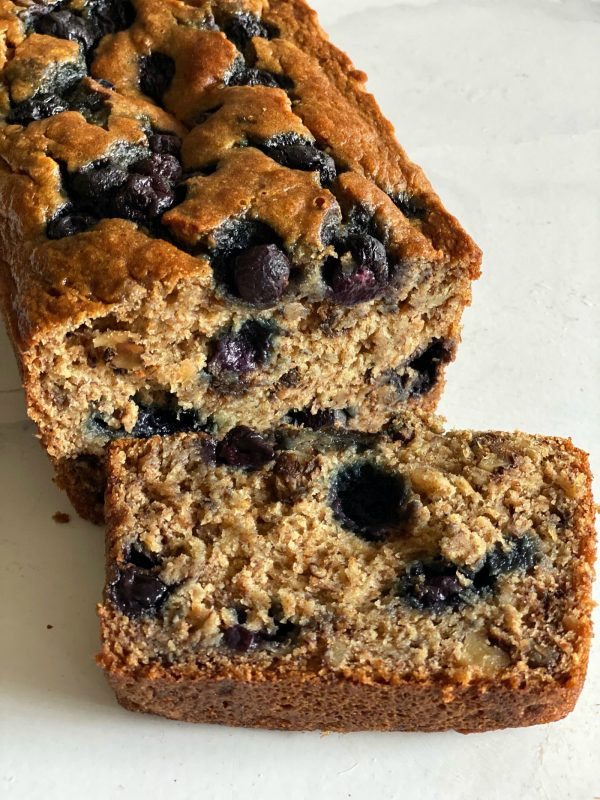 a loaf of banana blueberry bread with a close up of a slice