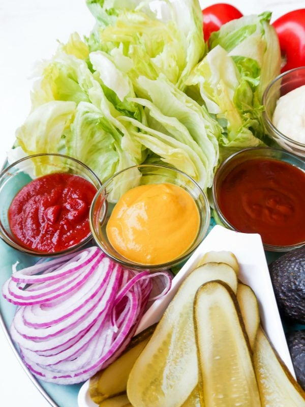 ketchup and mustard on a Basic Burger Condiment Platter, with red onion, pickles, iceberg lettuce