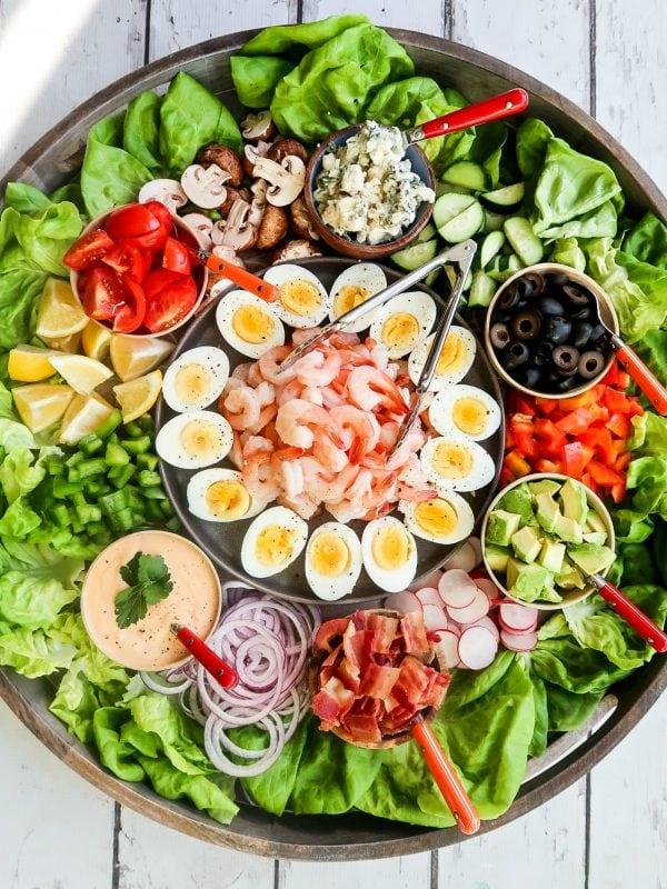 shrimp cobb salad ingredients on a big round board