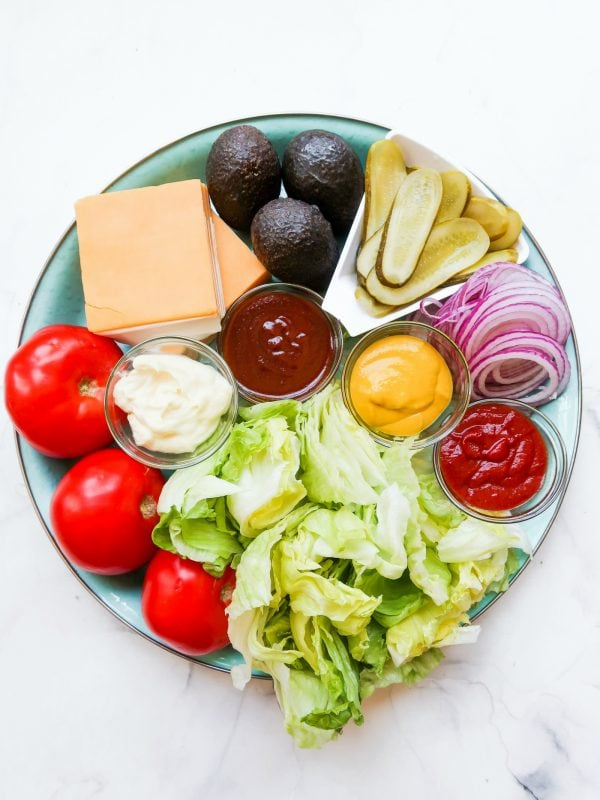 platter of iceberg lettuce, whole tomatoes, cheese, avocados, pickles, red onion, and condiments like mayo, mustard, ketchup, BBQ sauce