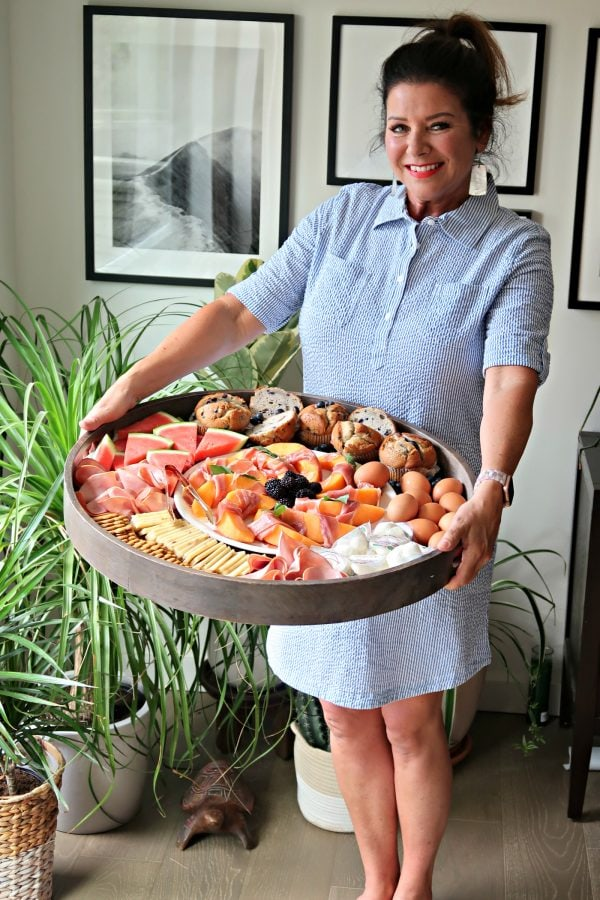 woman in striped dress holding a Ham Cheese Brunch Board