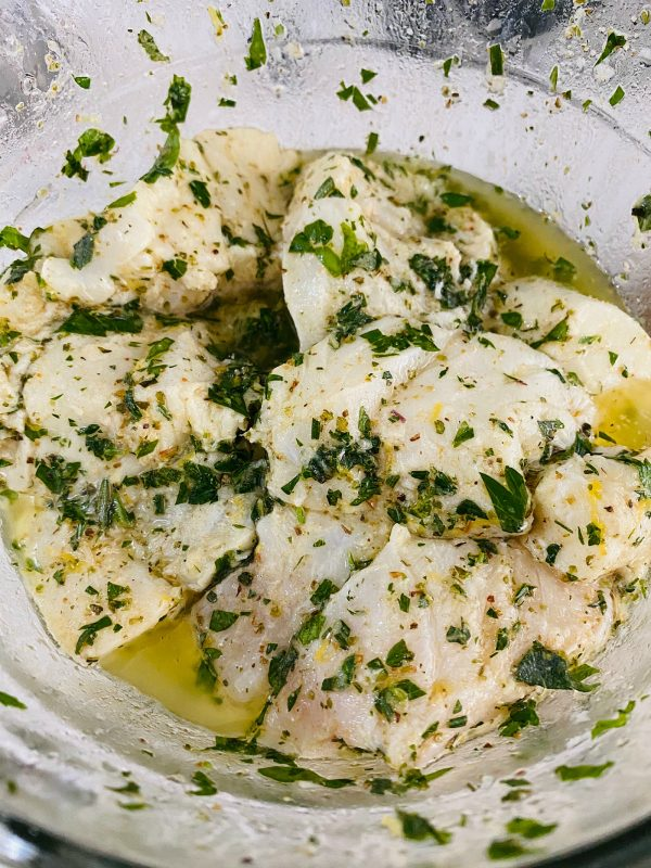 fish in marinade with fresh herbs