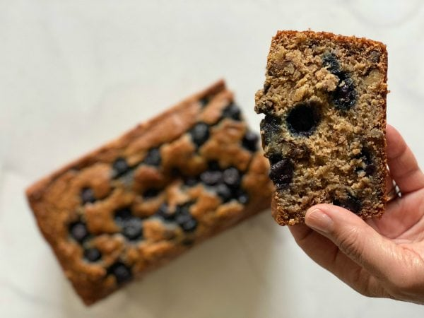 close up, a hand holding a slice of banana blueberry bread