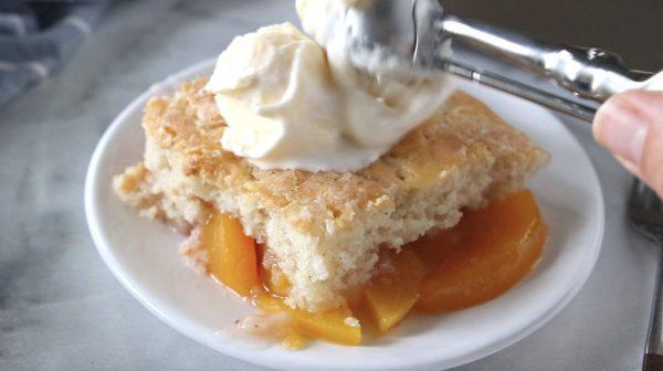 square piece of peach cobbler with ice cream