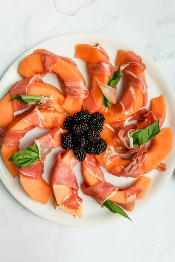 beautiful plate of Prosciutto-Wrapped Melon slices with fresh basil