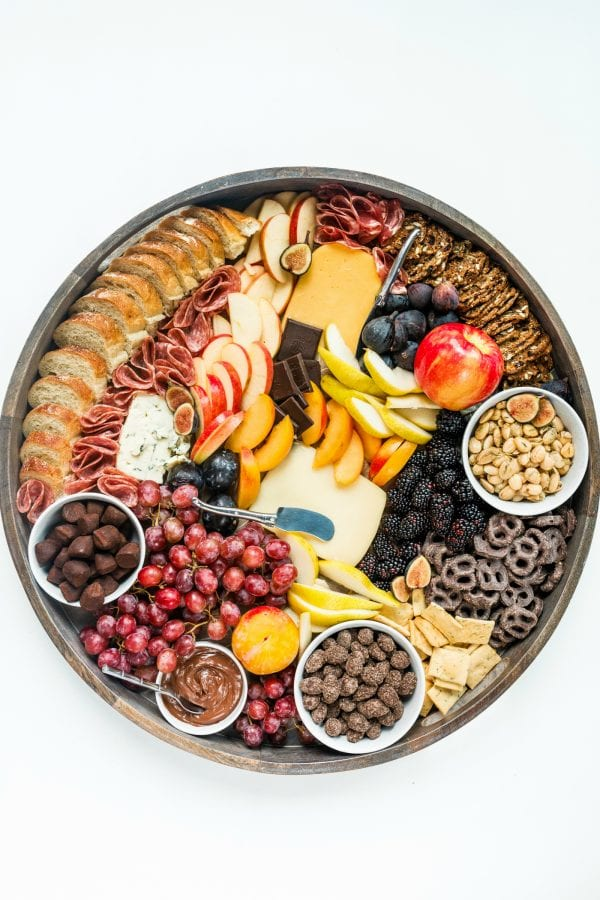 a round fall charcuterie board with cheese, crackers, meat, and fruit