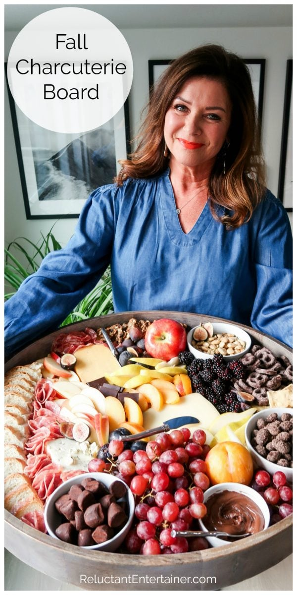 woman in a blue blouse holding a big round fall charcuterie board
