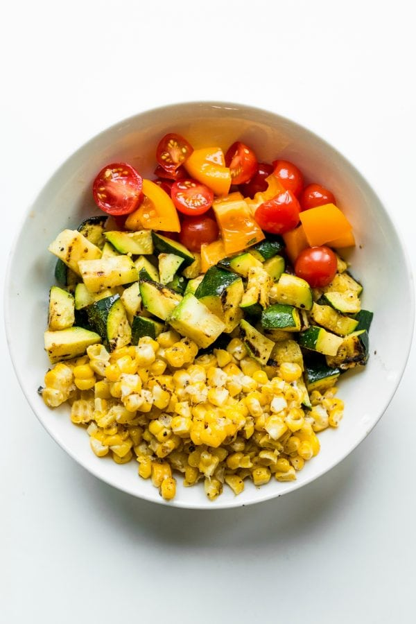 deconstructed corn, zucchini, tomatoes, in a large white bowl