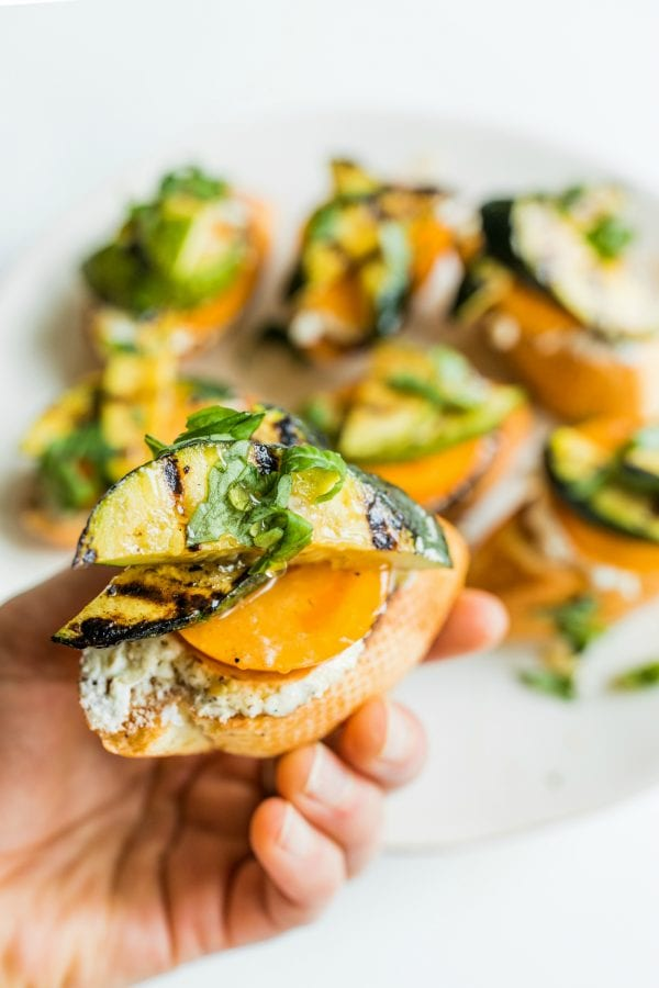 holding a grilled zucchini toast