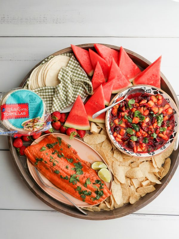 salmon, taco shells, chips on a round dinner board
