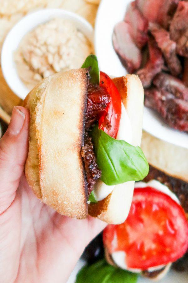 a caprese steak sandwich on a small french roll