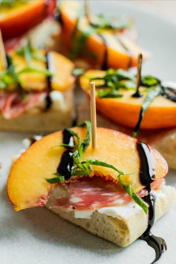 focaccia bread with a slice of nectarine and salami, with basil and balsamic drizzle