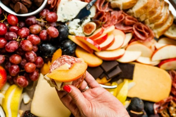 holdling a cracker with salami, Grand Cru cheese, and a nectarine