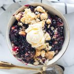 round bowl of blueberry crunch with vanilla ice cream