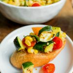 a piece of crostini toast with grilled corn, tomato, zucchini chopped in small pieces on top