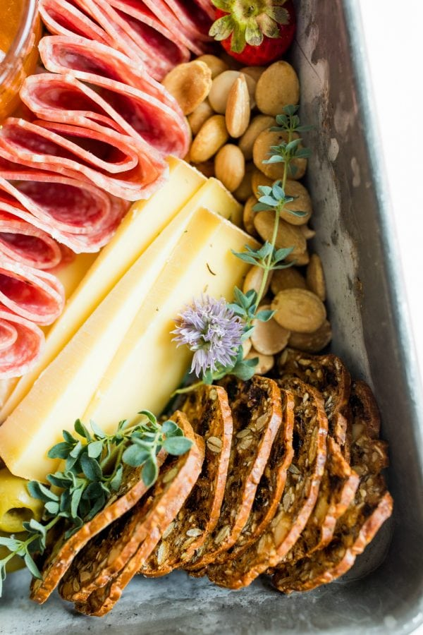 salami, cheese slices, crackers, nuts in a pan