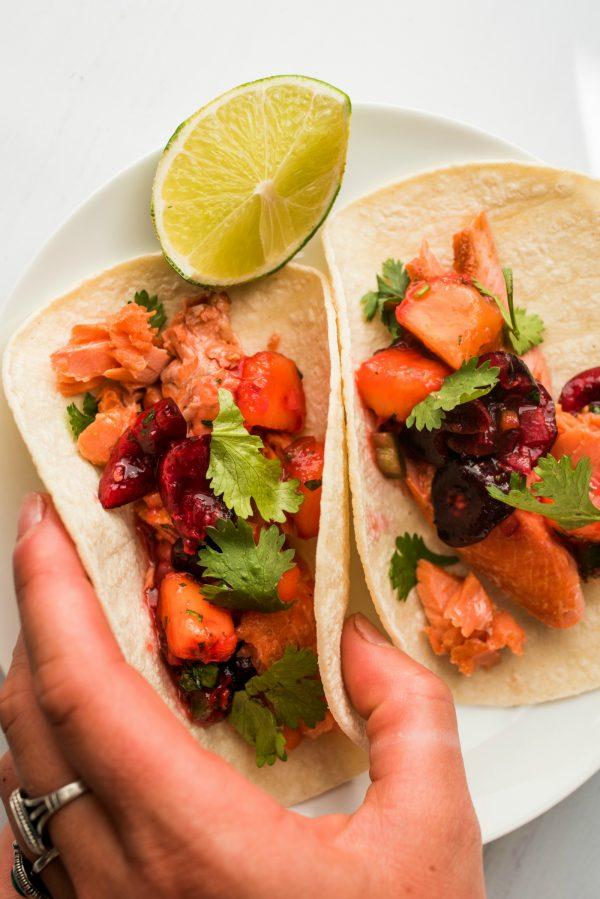 holding 2 salmon tacos with cherry peach salsa
