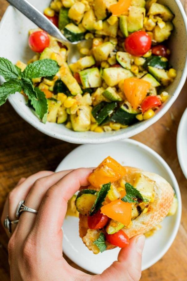 holding upclose a Grilled Zucchini Corn Crostini
