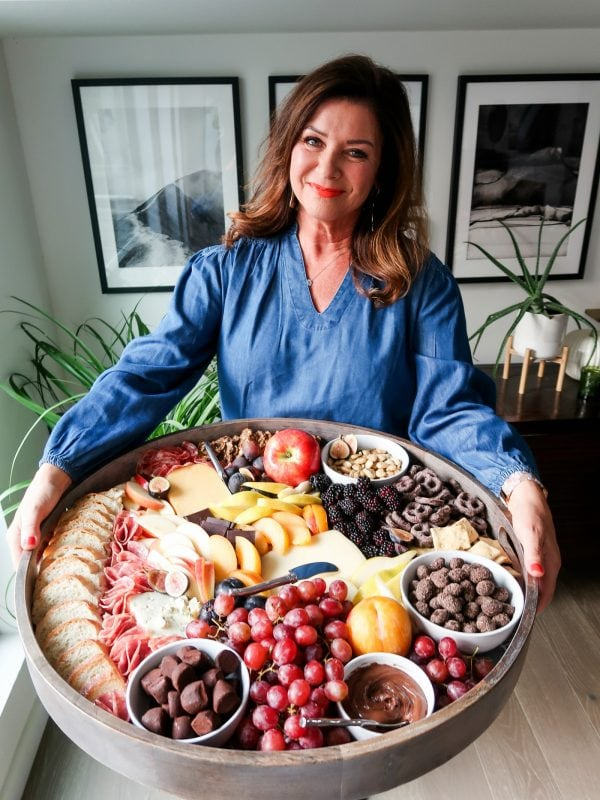 woman holding a round epic fall cheese board