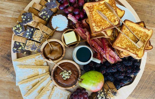 a beautiful breakfast spread with french toast, bacon sweets