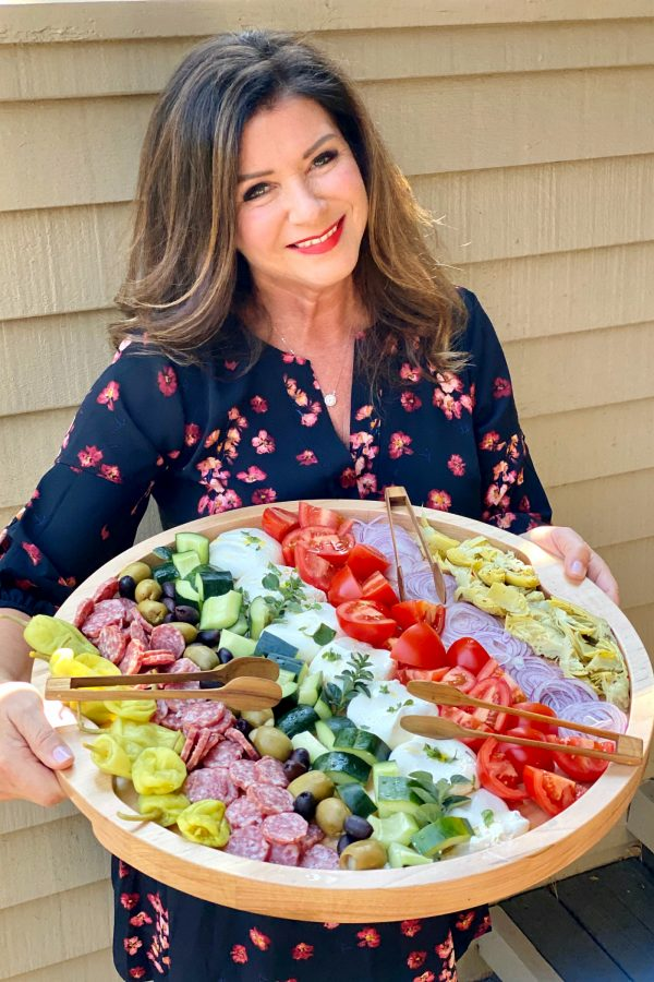 woman holding a round wood tray with deconstructed burrata choopped salad