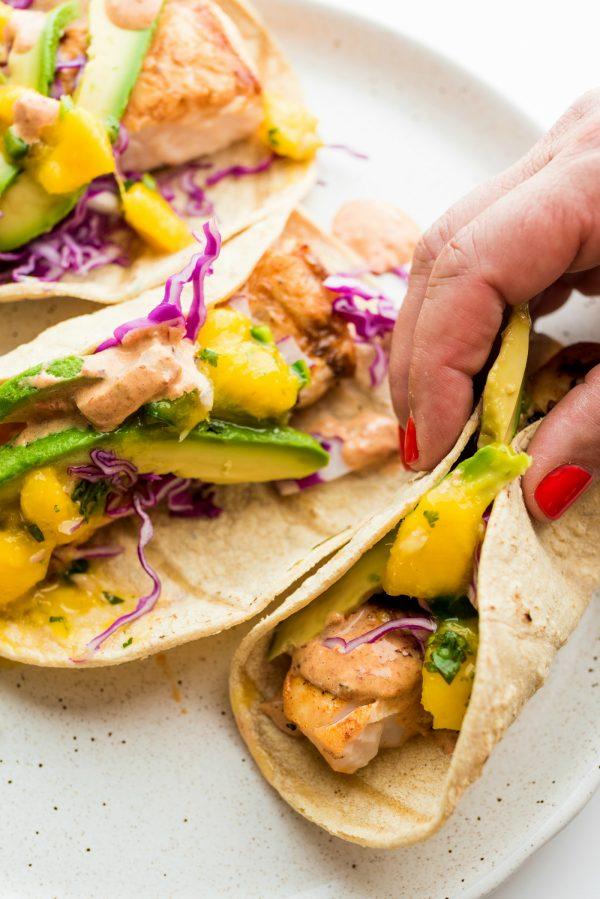 folding a mahi mahi taco with mango