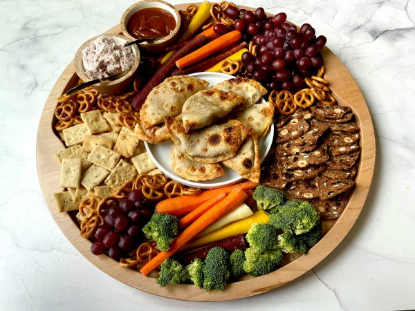 a round board with Pumpkin Empanadas, veggies, crackers, and dips