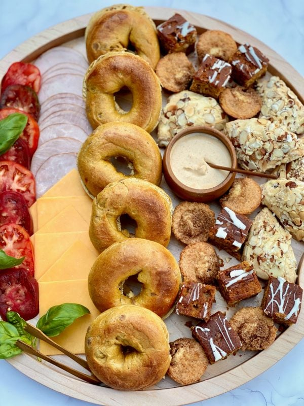 a round spread of pumpkin bagels, tomatoes, meat, cheesem and sweets