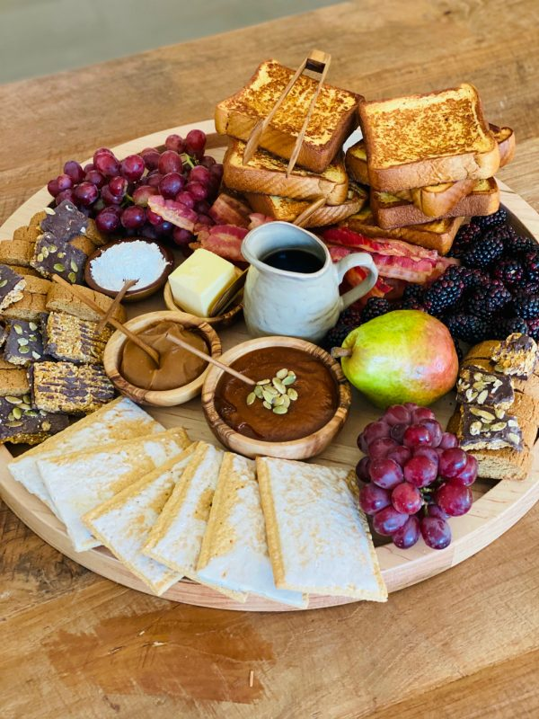beautiful breakfast spread on a round board with brioche french toast