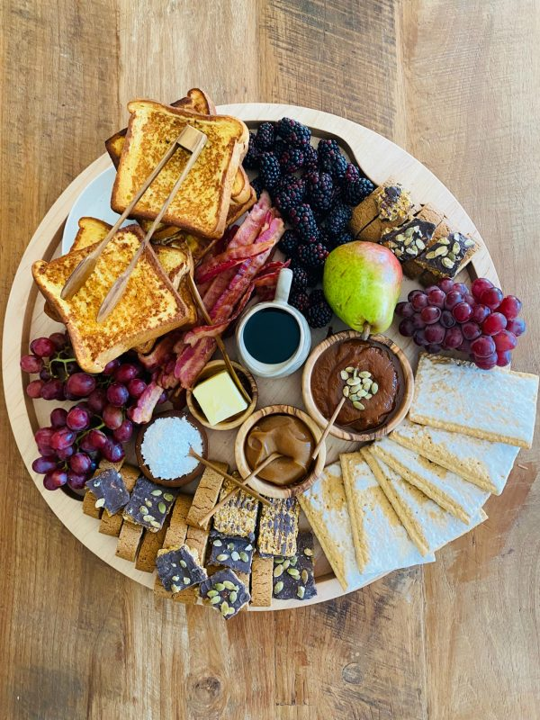 round breakfast tray with french toast, fruit, bacon, sweets