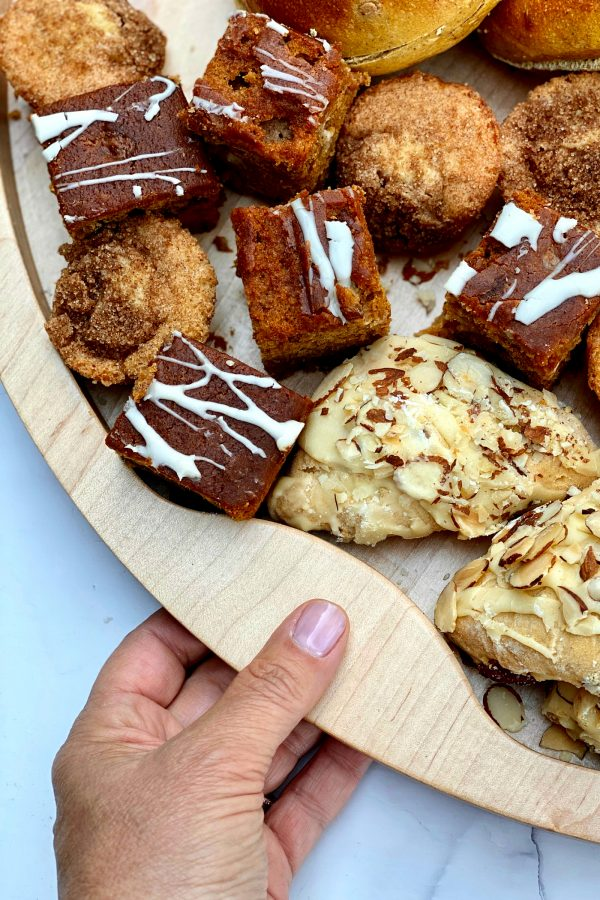 holding a wood board filled with breakfast scones