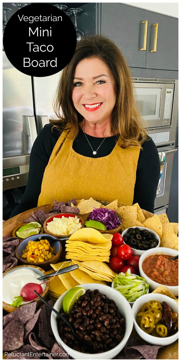 woman wearing a yellow smock apron holding a vegetarian taco dinner board