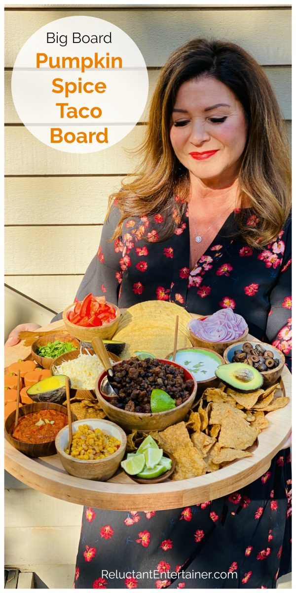 woman holding a round wood board with pumpkin spice taco ingredients
