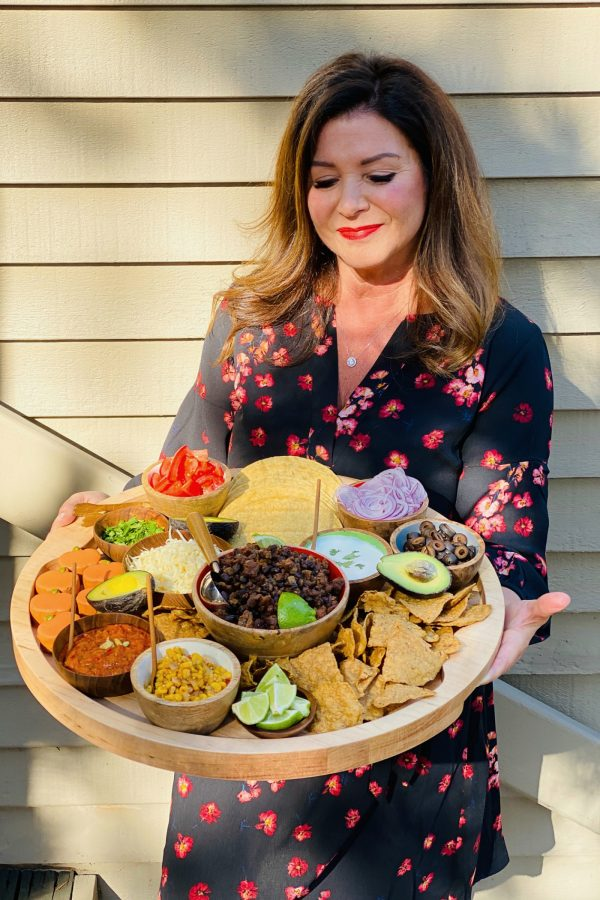 woman holding a round board with pumpkin taco ingredients